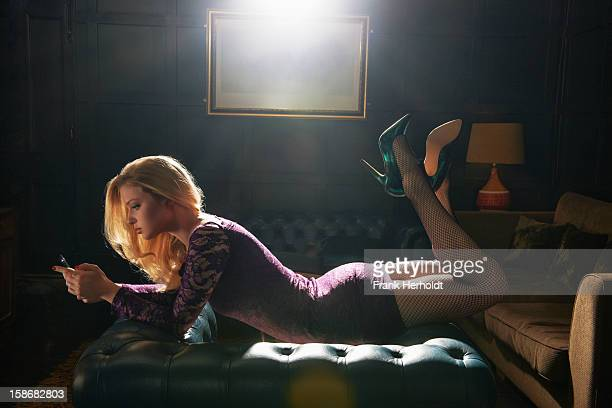 Woman lying on top of armchair with phone