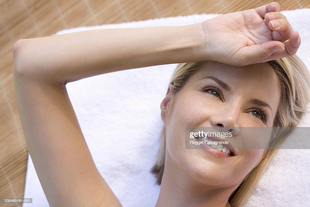 Woman lying on towel, hand on forehead, smiling, close-up : Stock Photo