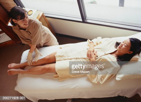 Woman lying on treatment table having leg wax