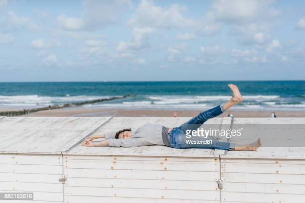 Woman lying on wooden box on the beach