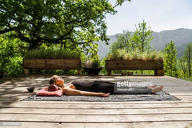 Woman lying on wooden terrace meditating