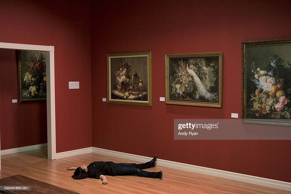 Woman lying unconscious on art gallery floor : Stock-Foto