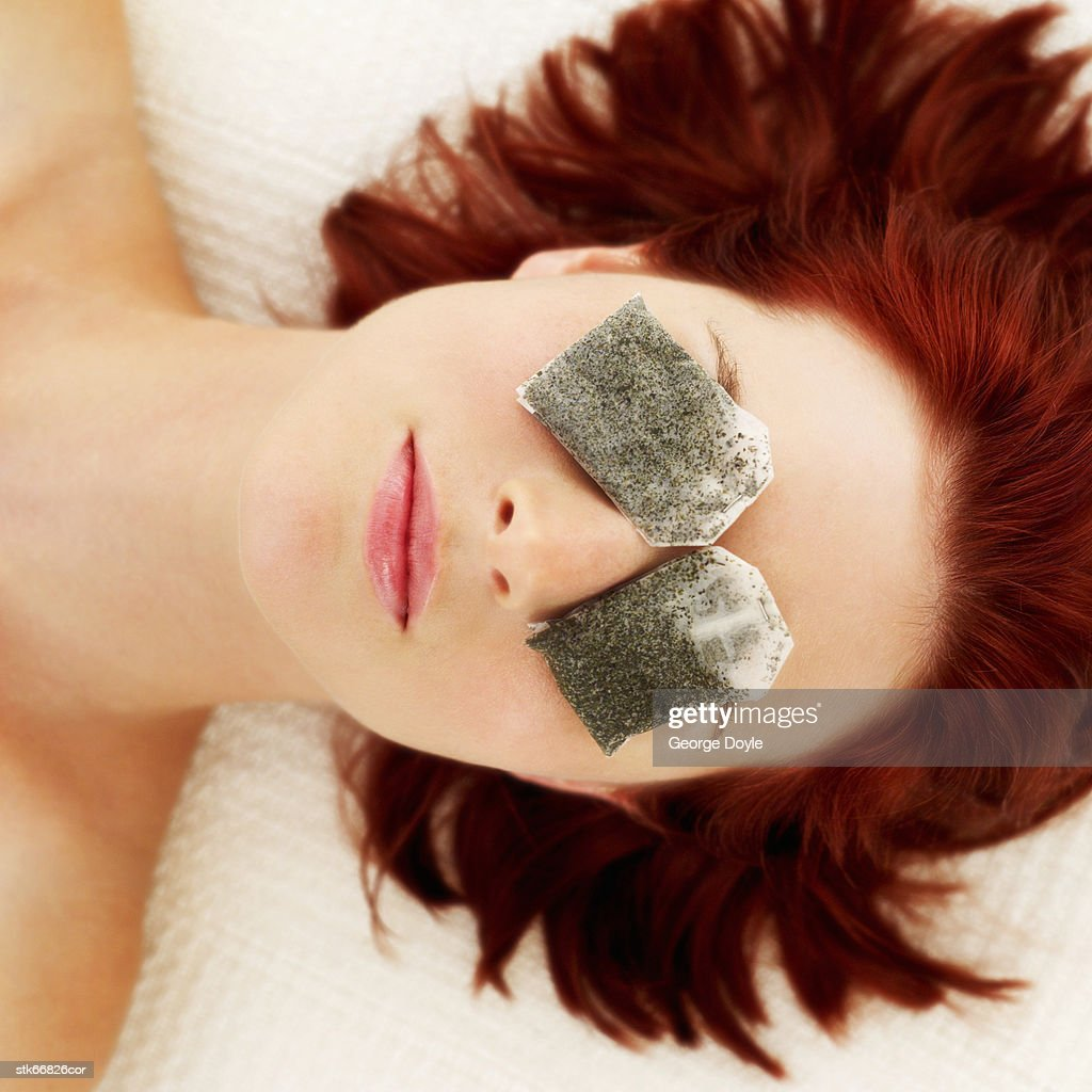 woman lying with tea bags on her eyes : Stock Photo