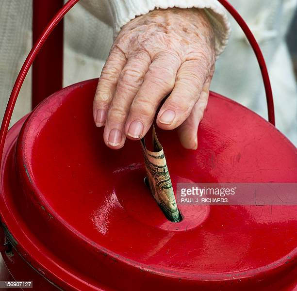 A woman makes a donation into a Salvation Army kettle outside a Giant grocery store November 24 in Clifton Virgina Salvation Army volunteers...