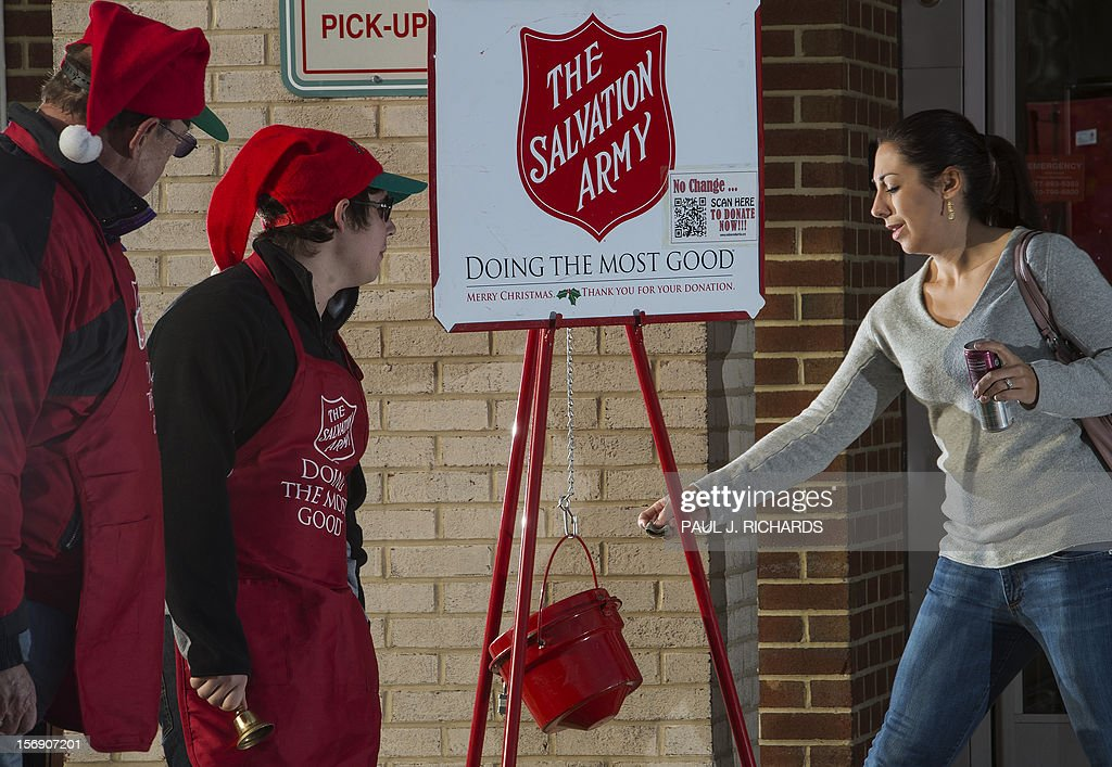 A woman makes a donation into a Salvation Army kettle outside a Giant grocery store November 24 in Clifton Virgina as bell ringers William Schmidt...