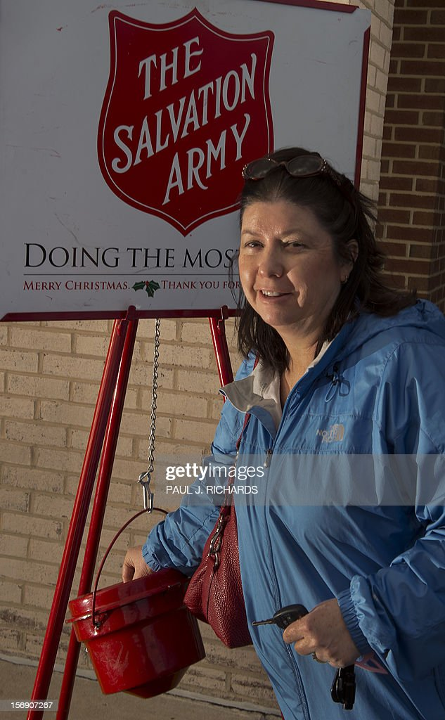 A woman makes a donation into a Salvation Army kettle outside a Giant grocery store November 24, 2012, in Clifton, Virgina. Bell ringers William Schmidt, who has worked as a volunteer for 20 years here, and his grandson Bubba Wellens (neither seen) volunteer for the Salvation Army to collect donations from holiday shoppers for the needy between Thanksgiving and Christmas. Schmidt does it all 'to teach others the joy of giving'. AFP Photo/Paul J. Richards
