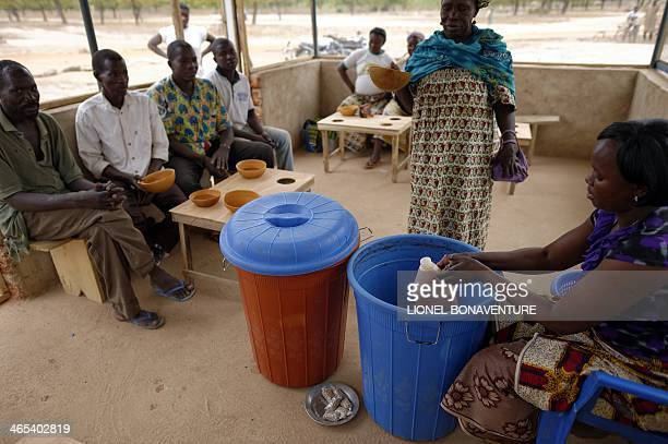 A woman makes a local beer called 'Dolo' on January 24 2014 brewed by women thanks to a microcredit program funded by the French cosmetics company...
