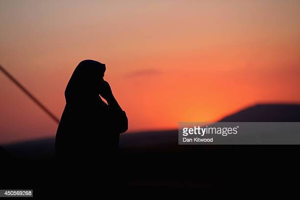 A woman makes a phonecall outside her tent at a temporary displacement camp set up next to a Kurdish checkpoint on June 13 2014 in Kalak Iraq...