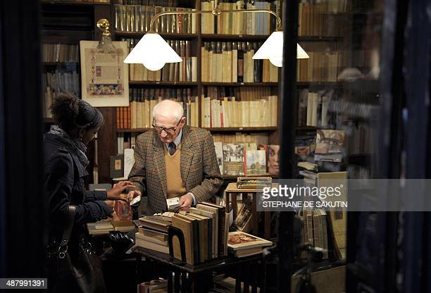 A woman makes a purchase at a bookshop at Galerie Vivienne in Paris on May 3 2014 AFP PHOTO / STEPHANE DE SAKUTIN