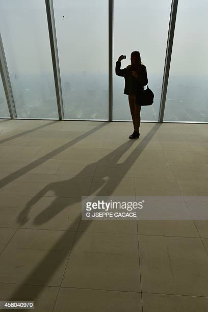 A woman makes a 'selfie' behind the windows of the 'City Life office Tower' a skyscraper of Japanese architect Arata Isozaki under construction in...