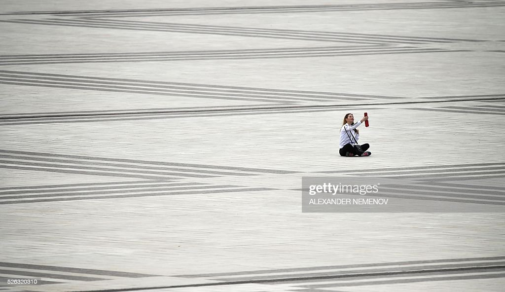 A woman makes a selfie picture in front of the track at the Sochi Autodrom circuit on April 30, 2016. / AFP / ALEXANDER