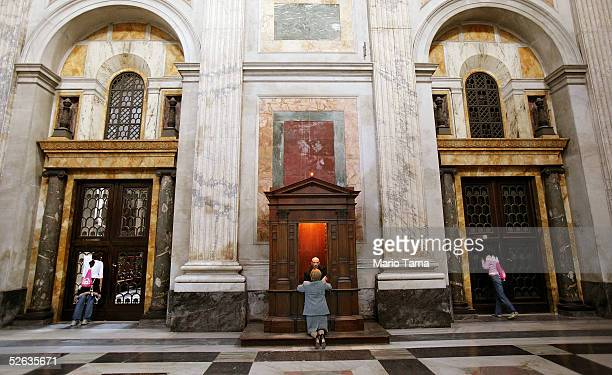 A woman makes confession with a priest as girls take in the scenery at Saint Paul's Basilica during the interregnum period before the conclave April...