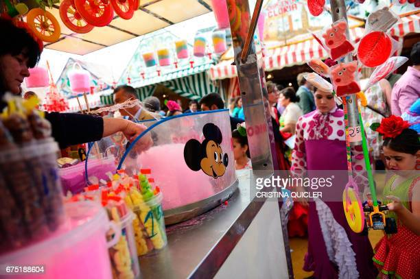 A woman makes cotton candy during the 'Feria de Abril' in Sevilla on April 30 2017 The fair dates back to 1847 when it was originally organized as a...