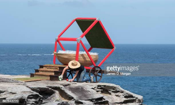A woman makes final touches to 'Aqua Gold of the future' at Sculpture By The Sea on October 18 2017 in Sydney Australia The annual art event draws...