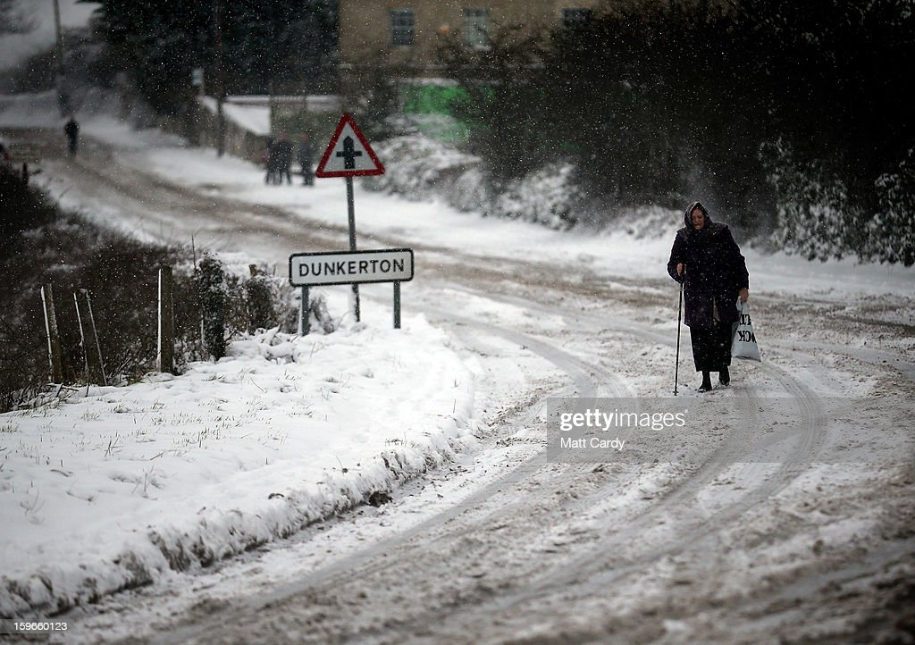 A woman makes her away along the normally busy A367 between Bath and Peasedown St John on January 18, 2013 near Bath, England. Heavy snow is bringing widespread disruption to many parts of the UK.