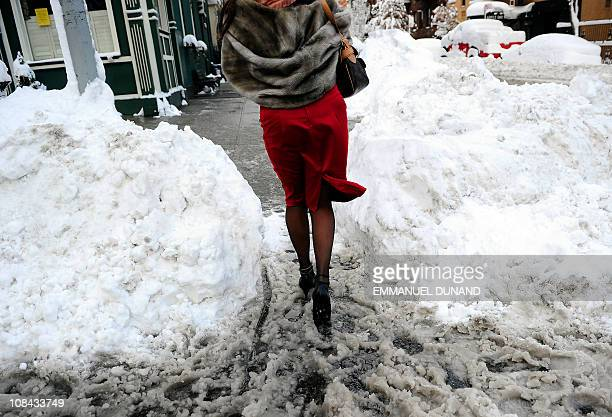 A woman makes her way after heavy snow falls in New York January 27 2011 New York shut down two airports public schools and most city services in the...