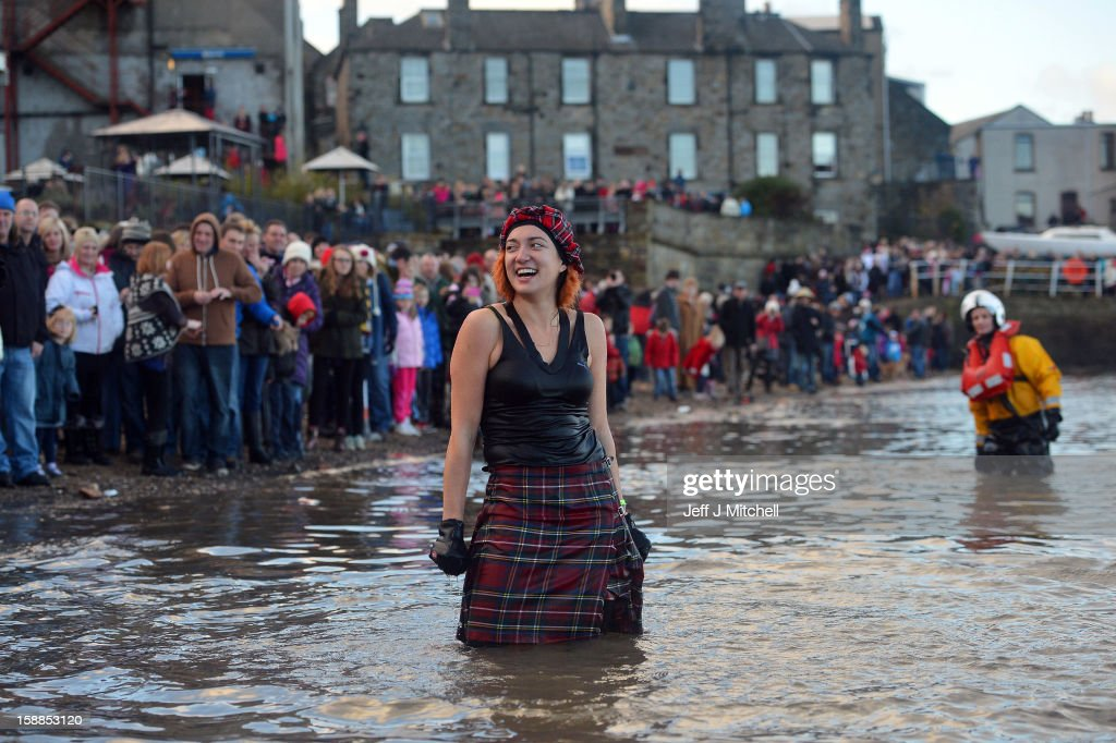 A woman makes her way in the water wearing a kilt as she joined around 1,000 New Year swimmers, many in costume, braved freezing conditions in the River Forth in front of the Forth Rail Bridge during the annual Loony Dook Swim on January 1, 2013 in South Queensferry, Scotland. Thousands of people gathered last night to see in the New Year at Hogmanay celebrations in towns and cities across Scotland..