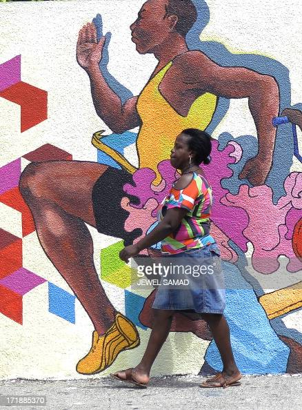 A woman makes her way past a wall painted depicting Jamaican culture in downtown Kingston on June 29 2013 Major sectors of the Jamaican economy...