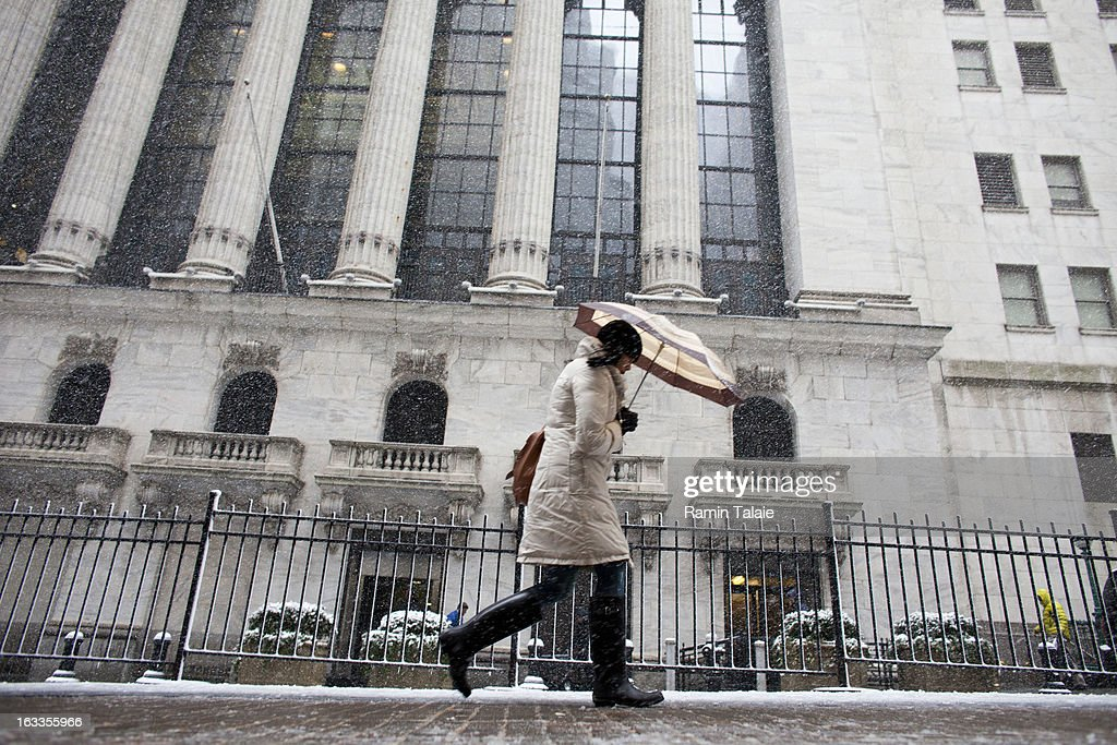 A woman makes her way past the New York Stock Exchange in the snow on March 8, 2012 in New York City. The storm part of the same system that pummeled the Midwest is expected to dump one to two inches of snow in the New York Metro area.