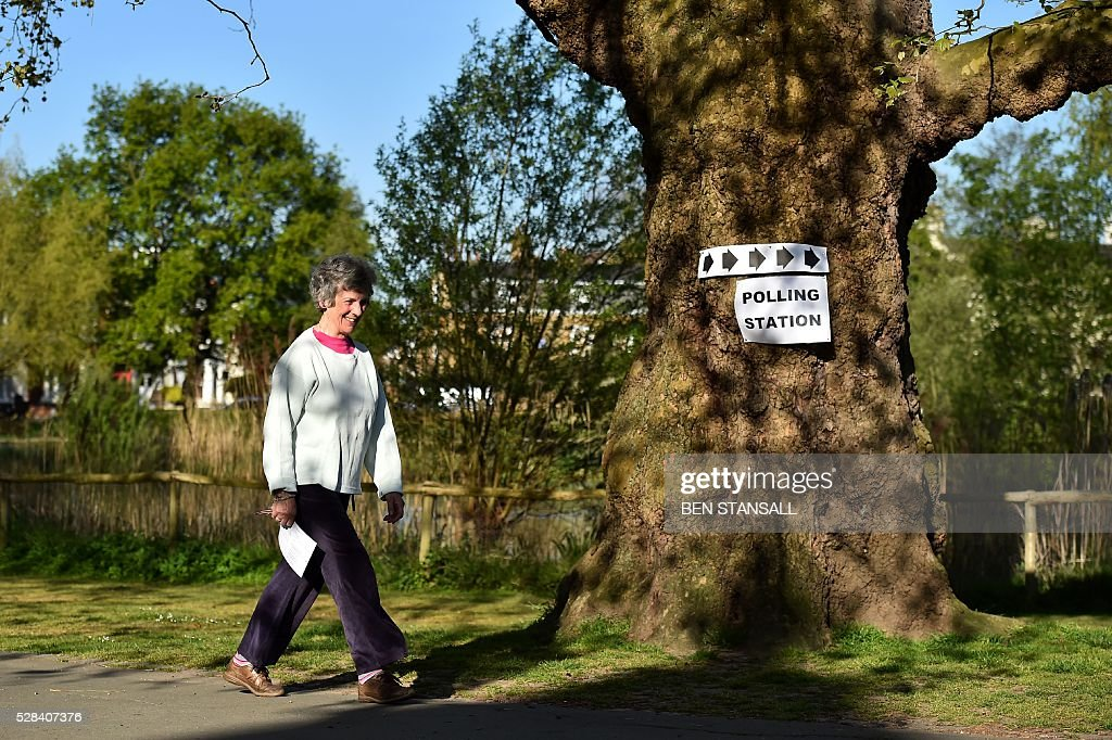 A woman makes her way to cast her vote at a Polling Station in Barnes, south-west London on May 5, 2016. Londoners go to the polls on Thursday to elect their new mayor following a bitter campaign between the two leading candidates, Goldsmith, and Labour's Sadiq Khan, that stayed ugly to the very end. While London chooses a new mayor, there are also elections to the Scottish, Welsh and Northern Irish assemblies, and 124 local authorities scattered across England. / AFP / BEN