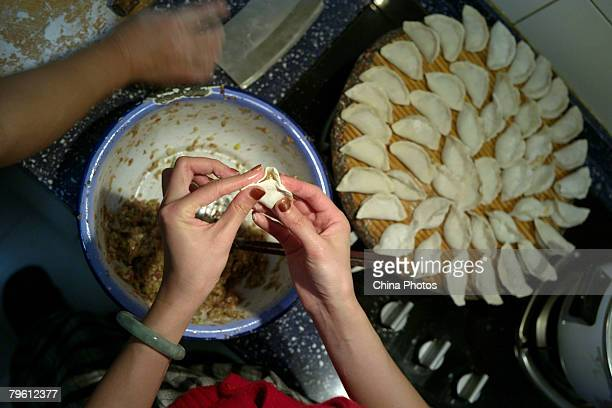 A woman makes Jiaozi or dumplings on the lunar new year eve February 6 2008 in Beijing China Making dumplings with families is one of the major...
