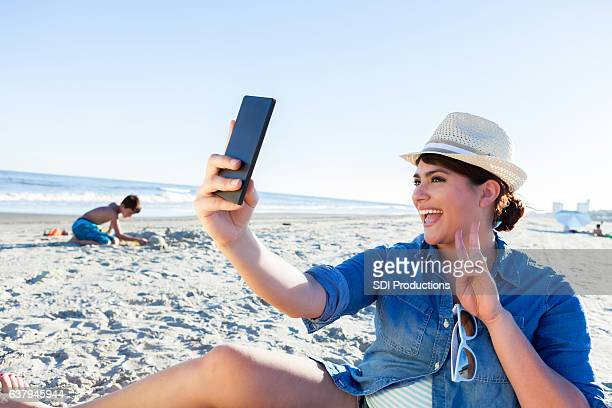 Woman makes peace sign while taking selfie on the beach
