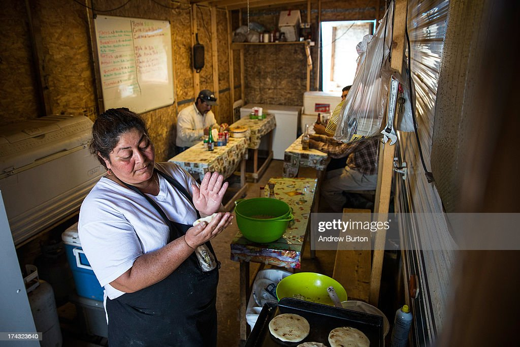 A woman makes tortillas in a make-shift restaurant, constructed of plywood and two-by-fours and attached to an RV, on July 23, 2013 outside Watford City, North Dakota. North Dakota has been experiencing an oil boom in recent years, due in part to new drilling techniques including hydraulic fracturing and horizontal drilling. In April 2013, The United States Geological Survey released a new study estimating the Bakken formation and surrounding oil fields could yield up to 7.4 billion barrels of oil, doubling their estimate of 2008, which was stated at 3.65 billion barrels of oil.