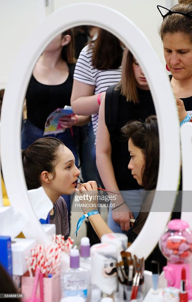 A woman makes up a girl during the Get Beauty fair, a beauty and fashion fair inspired by the US 'Beautycon' event gathering of fashion bloggers and YouTube personalities, on May 28, 2016 at the Vincennes' parc floral, eastern Paris. / AFP / FRANCOIS