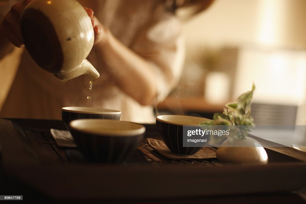 A woman making a cup of tea : Stock Photo