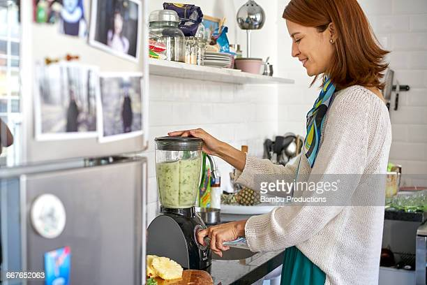 Woman making a green juice at kitchen