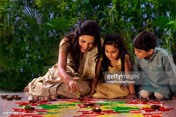Woman making a rangoli with her kids