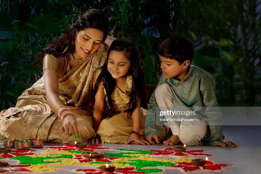 Woman making a rangoli with her kids