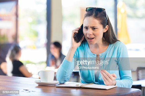 Woman making angry phone call in local coffee shop