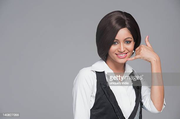 Woman making call me gesture and smiling