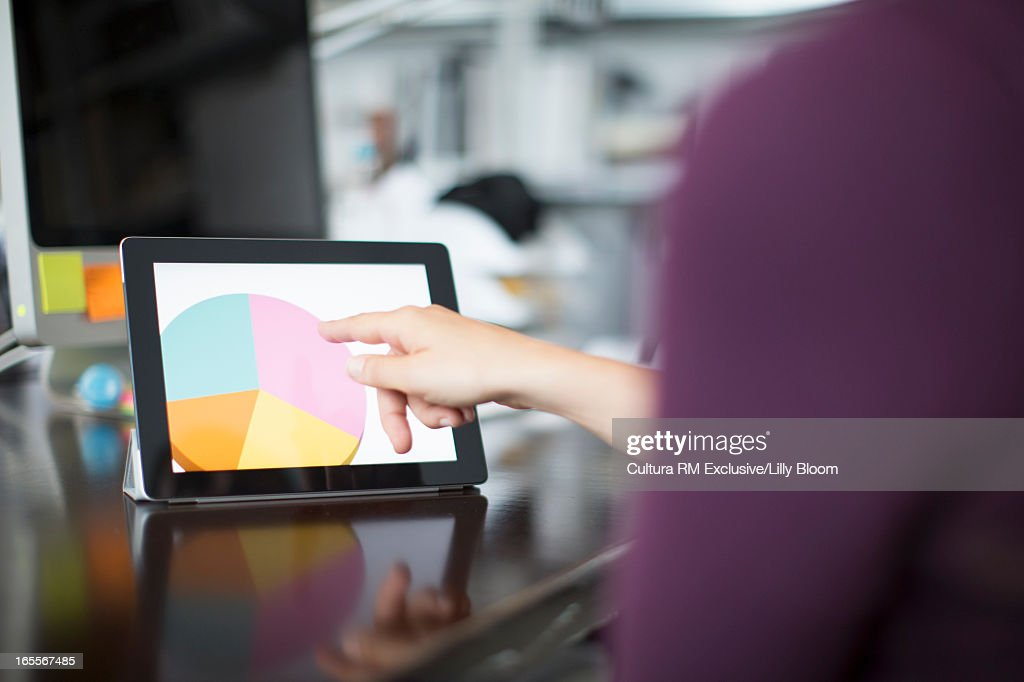 Woman making chart on tablet computer : Stock Photo