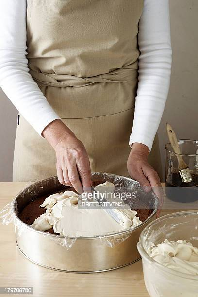 Woman making chocolate cake, spreading cream