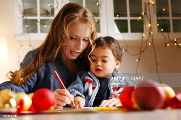 Woman making Christmas drawings with her son