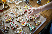 Woman making Christmas gingerbread cookies in kitchen