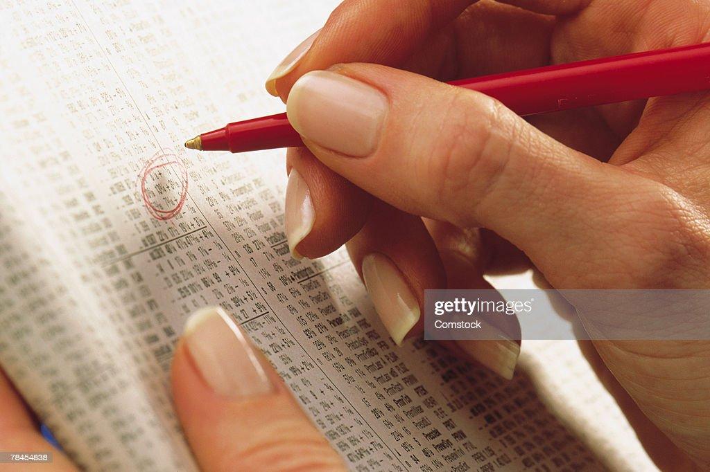 Woman making circling stocks in newspaper listing