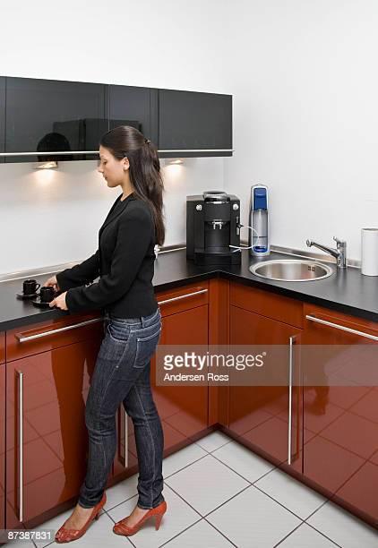 Woman making coffee in office kitchen