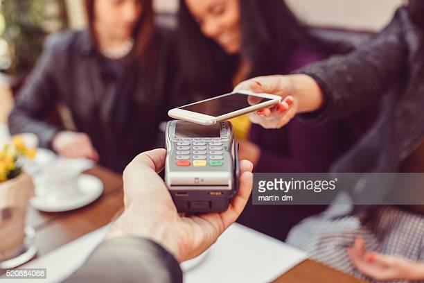 Femme faisant de paiement sans contact avec un smartphone