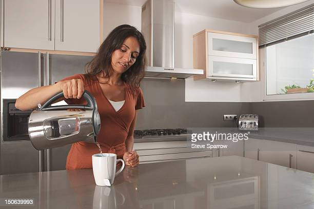 Woman making cup of tea in kitchen