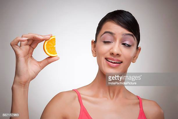 Woman making face at orange segment over colored background
