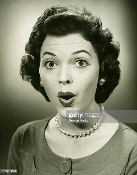 Woman making face in studio, (B&W), close-up, portrait