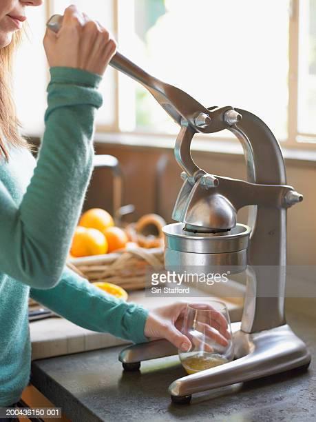 Woman making fresh orange juice in kitchen