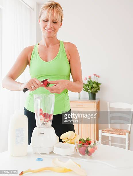 Woman making fruit smoothie at home