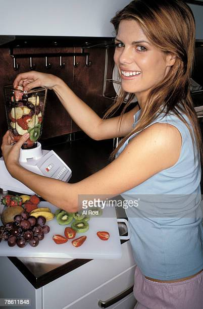 Woman making fruit smoothie in blender