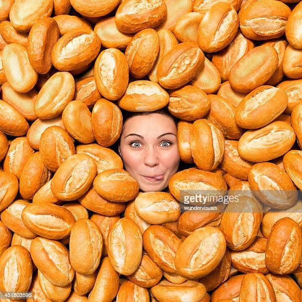 Frau machen lustiges Gesicht umgeben mit Brot