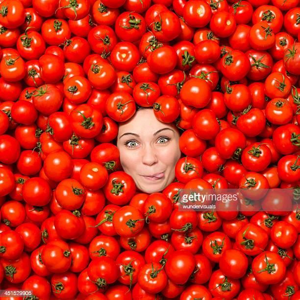 Frau machen lustiges Gesicht umgeben mit Tomaten