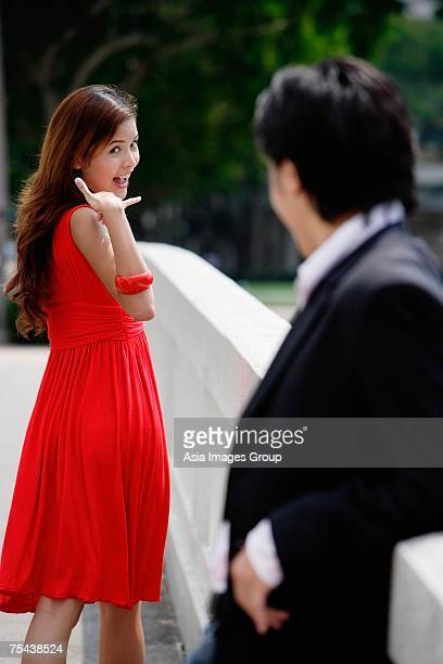 Woman making hand sign to man in foreground